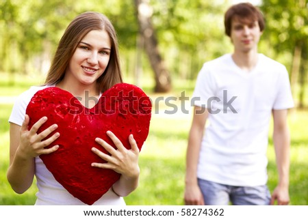 happy young girl holding big red heart, young man in background - stock photo