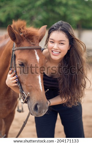 Happy young girl hugging a pony - stock photo