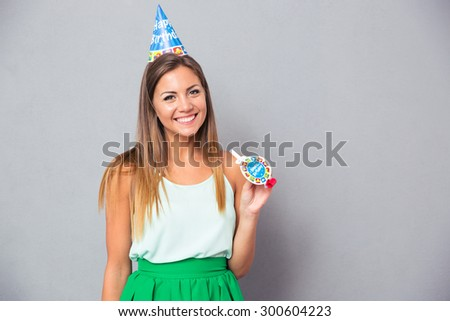 Happy young girl in birthday hat and whistle standing over gray background and looking at camera - stock photo