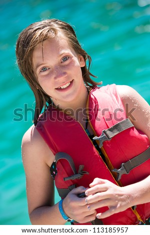 Happy young girl in life vest - stock photo