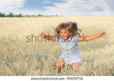 happy young girl in yellow field - stock photo