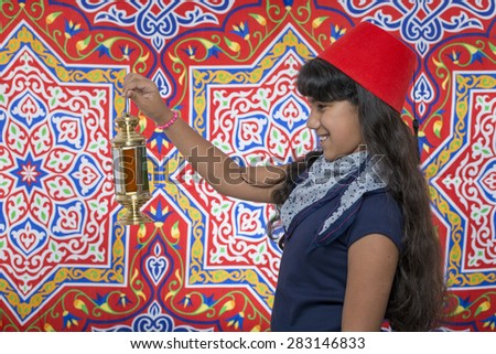 Happy Young Girl Looking at Lantern Celebrating Ramadan over Ramadan Fabric - stock photo