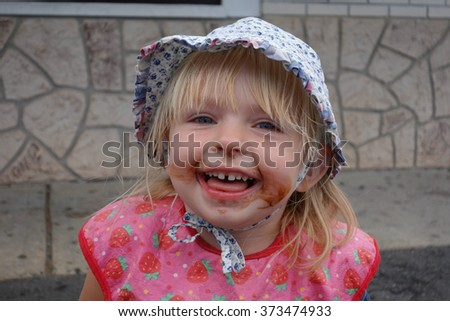 happy young girl loves ice cream smiles with messy dirty face - stock photo