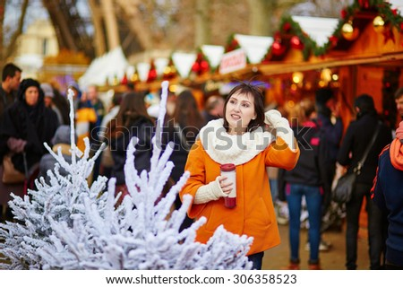 Happy young girl on a Parisian Christmas market, selecting Christmas treats and drinking hot beverage - stock photo
