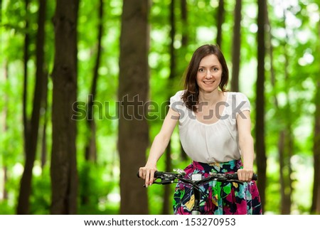 Happy young girl on bicycle in green summer park - stock photo