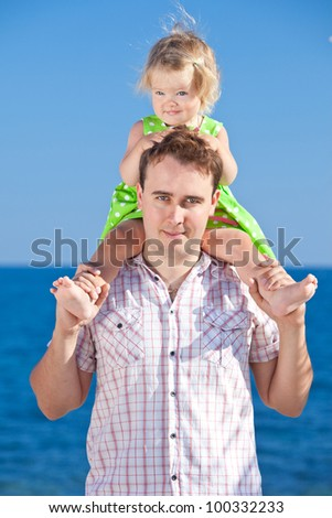 Happy young girl on her fathers shoulders on the beach - stock photo