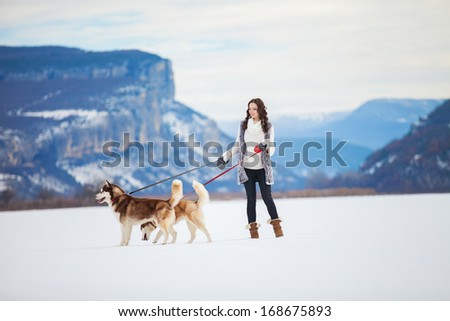 Happy young girl playing with siberian husky dogs in winter park. - stock photo