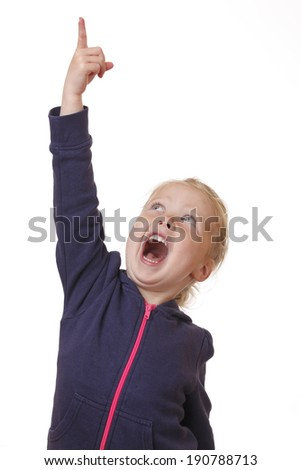 Happy young girl points finger in the air on white background - stock photo