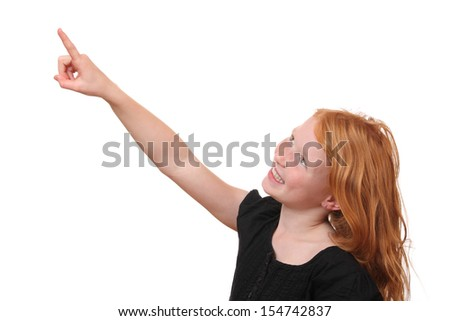 Happy young girl points up on white background - stock photo