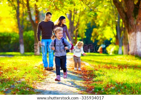 happy young girl running in autumn park with her family on background - stock photo