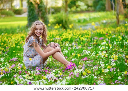Happy young girl sitting on the grass in park on a spring day - stock photo