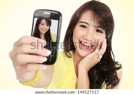 Happy young girl take the picture her self with handphone - stock photo