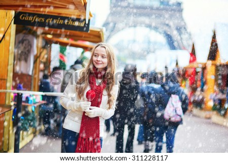 Happy young girl with caramel apple on a Parisian Christmas market with the Eiffel tower in the background during snowfall - stock photo