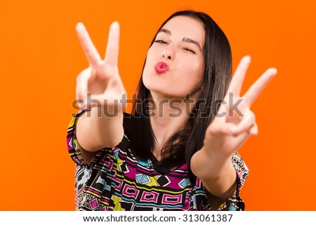 Happy young girl, with straight dark hair, wearing on colorful shirt, posing on the orange background, in studio, waist up - stock photo