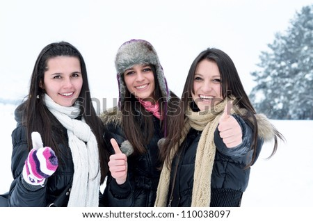 happy young girls are having fun in the snow - stock photo