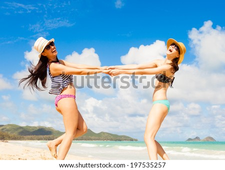 Happy young girls dancing on the beach. Beach party. - stock photo