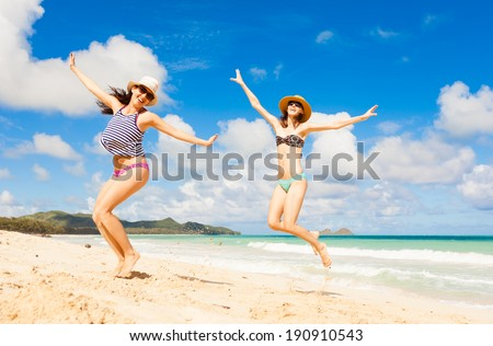 Happy young girls jumping at the beach. Summer beach fun. - stock photo