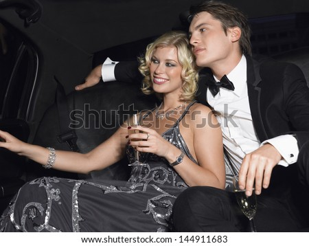 Happy young glamorous couple with champagne flutes in limousine - stock photo