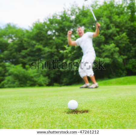 Happy young golfer after sending golf ball to the hole. Focus on ball. - stock photo