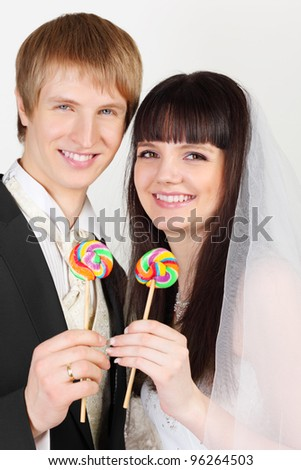 Happy young groom and bride hold colorful lollipops on white background - stock photo