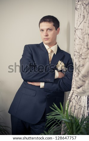 Happy young groom on his wedding day. Handsome caucasian man in tuxedo. A young, handsome guy, dark hair in a black suit. Portrait - stock photo