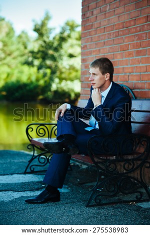 Happy young groom on their wedding day. Handsome groom thinking and putting on his bowtie while getting dressed for his wedding. Handsome caucasian man in tuxedo - stock photo