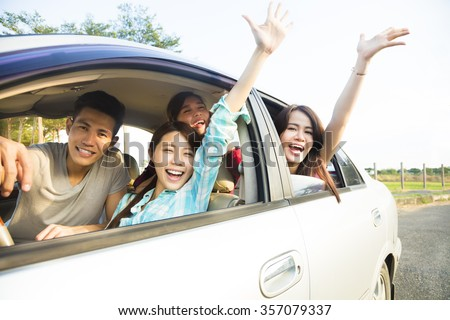 happy young group having fun in the car - stock photo