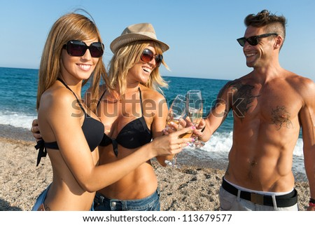 Happy young group of friends making a champagne toast on beach. - stock photo