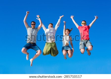Happy young group of people jumping in the blue sky - stock photo