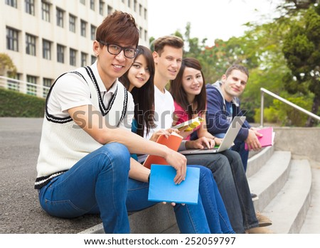 Happy  young group of students sitting on the stair - stock photo