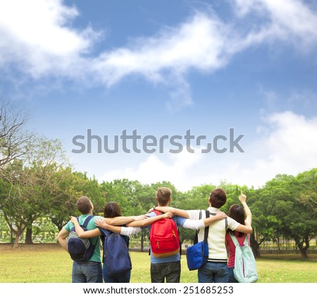Happy young group of students watching the sky  - stock photo