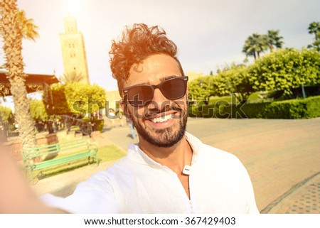 Happy young guy take selfie in sunglasses during holiday life moment. Hipster traveler wanderers enjoying exclusive alternative destination make souvenir photo during vacation in Marrakech. - stock photo