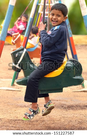 Happy young handsome boy ( kid ) playing on swing sets in a park. The photo shows summer time playground with a boy and other children swinging and enjoying their leisure time - stock photo