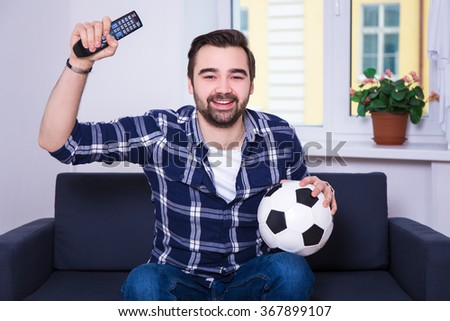 happy young handsome man watching football on tv at home - stock photo
