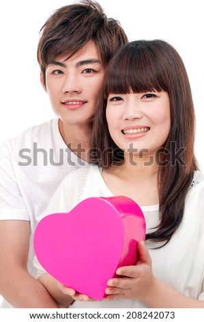 Happy young happy couple embracing holding heart gift box - stock photo