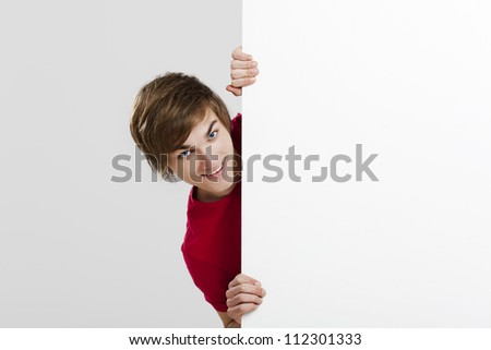 Happy young hiding and looking behind a blank white card - stock photo