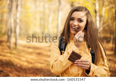 Happy young hiker woman eating chocolate  - stock photo