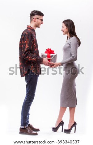 Happy young hipster couple with present isolated on a white background. Happy man give a gift to his girlfriend. Holiday . - stock photo