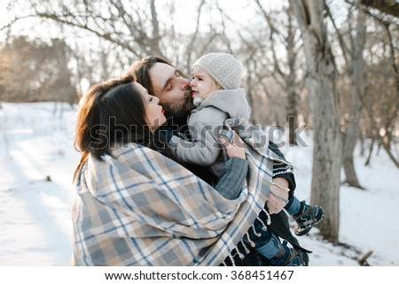 Happy young hipster family having fun, bowl, rising up, piggyback ride their children and relax in park on winter sunset - stock photo