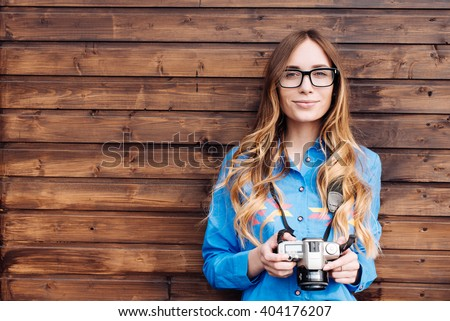 Happy young hipster woman in glasses holds retro photo camera - stock photo
