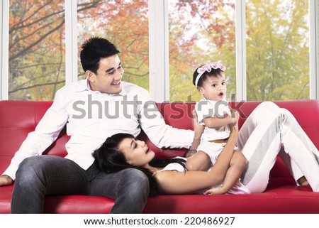 Happy young hispanic family playing on sofa at home in autumn - stock photo