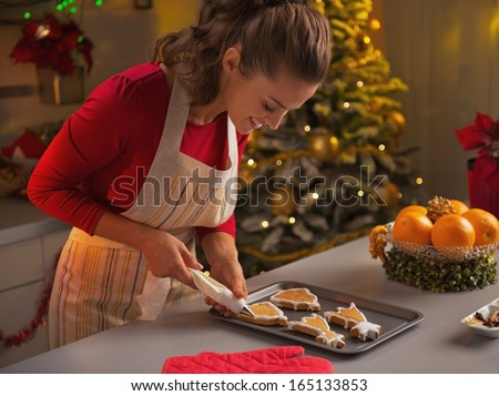 Happy young housewife decorating christmas cookies with glaze - stock photo