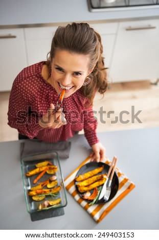 Happy young housewife eating while serving baked pumpkin - stock photo