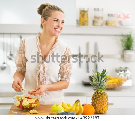 Happy young housewife making fruits salad - stock photo