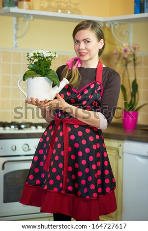 Happy young housewife taking care of the flowers - stock photo