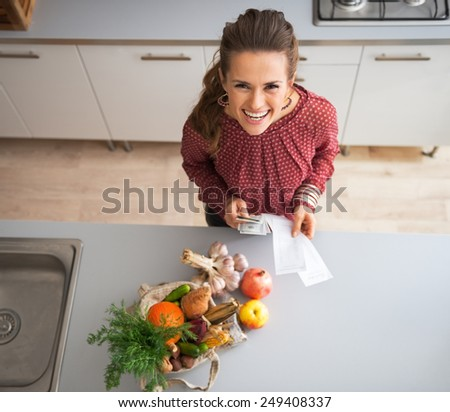Happy young housewife with money and grocery shopping checks after shopping on local market - stock photo