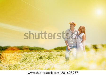 Happy,young hugging couple standing in a chamomile, daisy field.Lens flare, copy space - stock photo