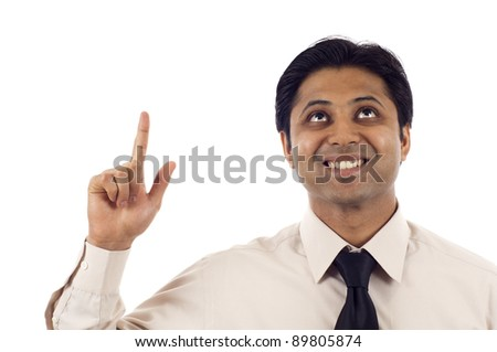 Happy young Indian businessman looking up and pointing at copyspace isolated over white background - stock photo
