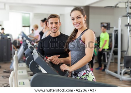 Happy young instructor talking to a woman who is on treadmill.  - stock photo