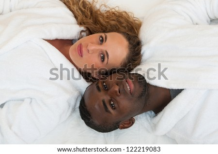 Happy young interracial couple lying in bed, top view. - stock photo